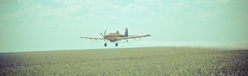 An airplane applying pesticide and/or fertilizer to a farm field