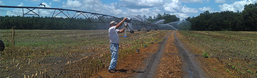 An MIL employee conducts an irrigation system evaluation.