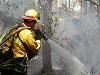 Photo: Florida Forest Serviceman using a fire hose to conduct wildfire management