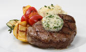 steak on a white plate with mashed potatoes, garnished with grape tomatoes and yellow squash.