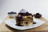 Stack of pancakes topped with blueberry sauce and whipped cream on a white plate with two bowl of blueberries on the side