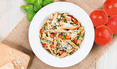 White bowl with pasta, red tomatoes, cheese, chicken and zucchini with red ripe tomatoes on the side with spinach leaves