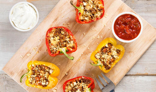 Red and yellow bell peppers on a wooden cutting board with sour cream and salsa with a fork.