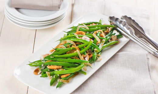 Snap Beans with Onions and Mushrooms on a white plate next to a stack of little plates.